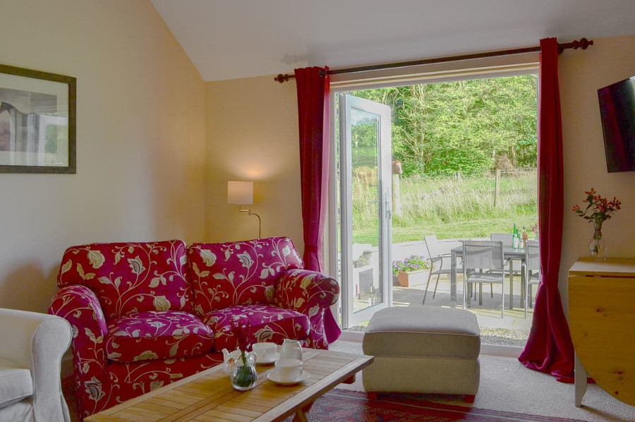 The living room at Belses Muir Shepherds Cottage has patio doors to the outside seating area; you have an open fire too