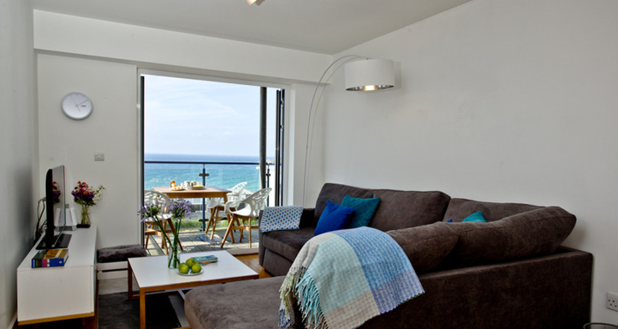 The living room with access to the balcony at Fistral Lookout