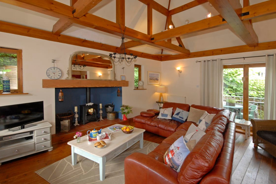 The living room with a wood burning stove at The Gower Beach Loft in Three Cliffs Bay